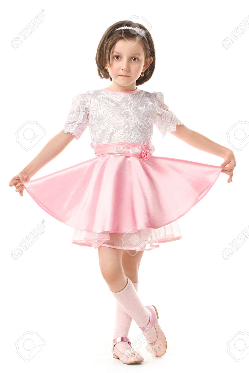 58762412212e Stock Photo - The lovely little girl posing in a beautiful pink dress.  Isolated over white background