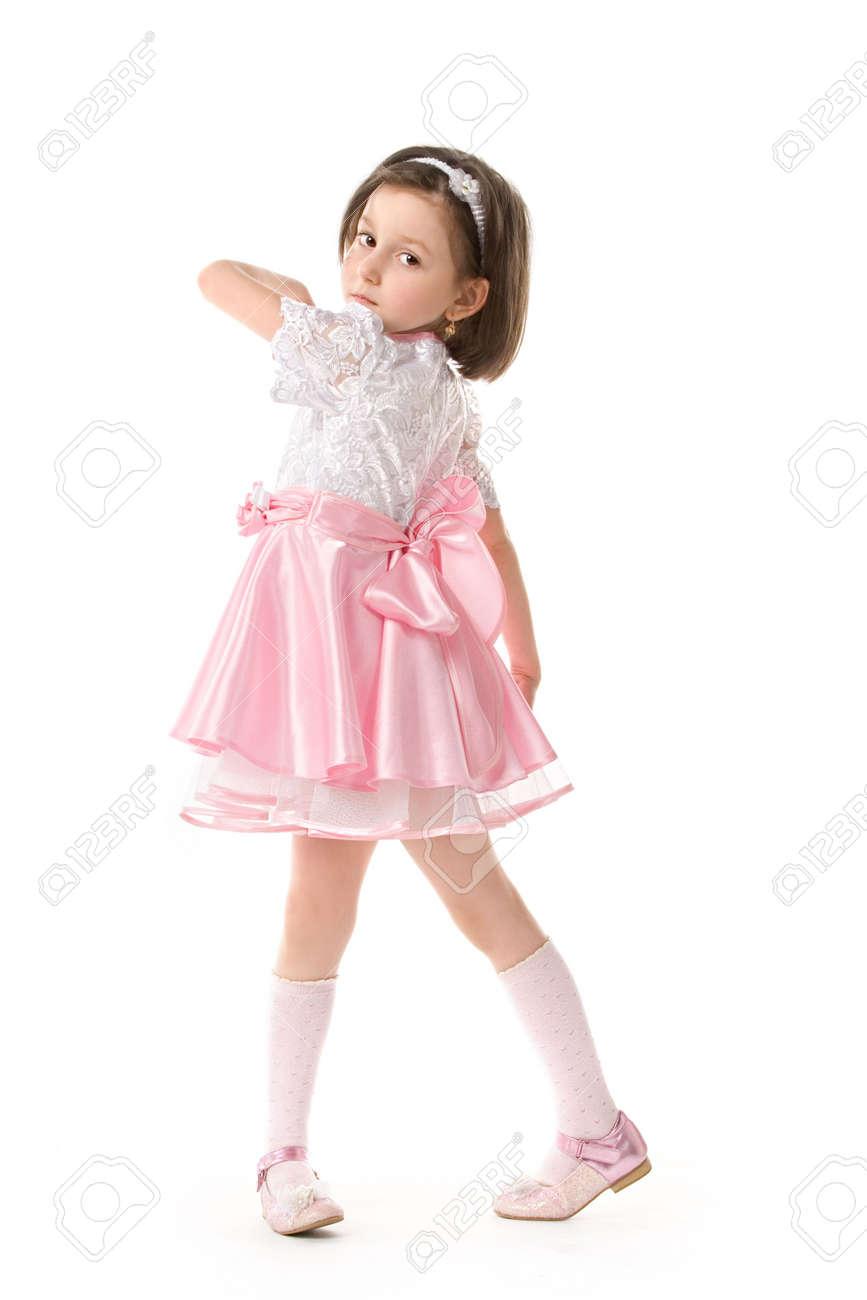 La encantadora niña posando en un hermoso vestido rosa. Aisladas más de fondo blanco