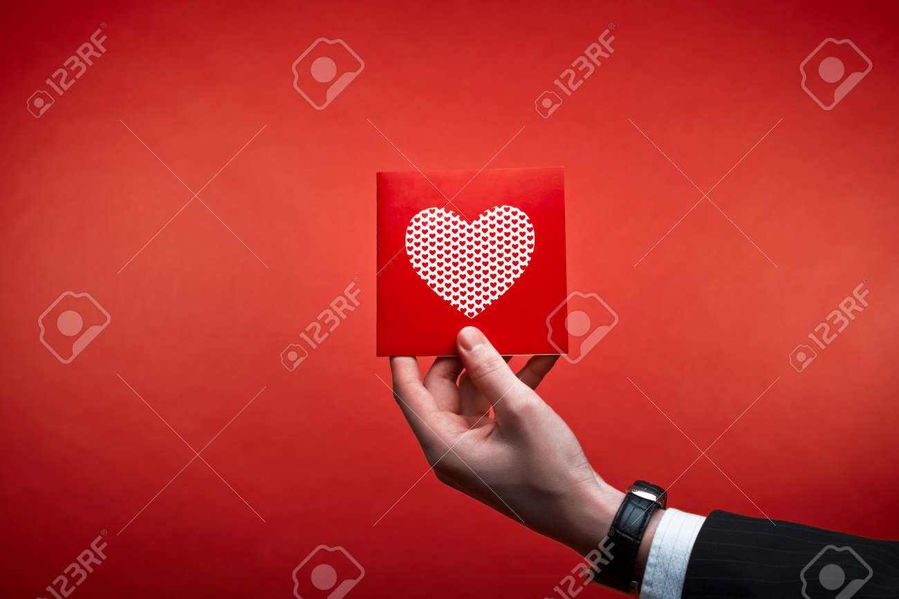 Male hand holding red Valentines card with heart on a pink background Stock Photo - 15138815