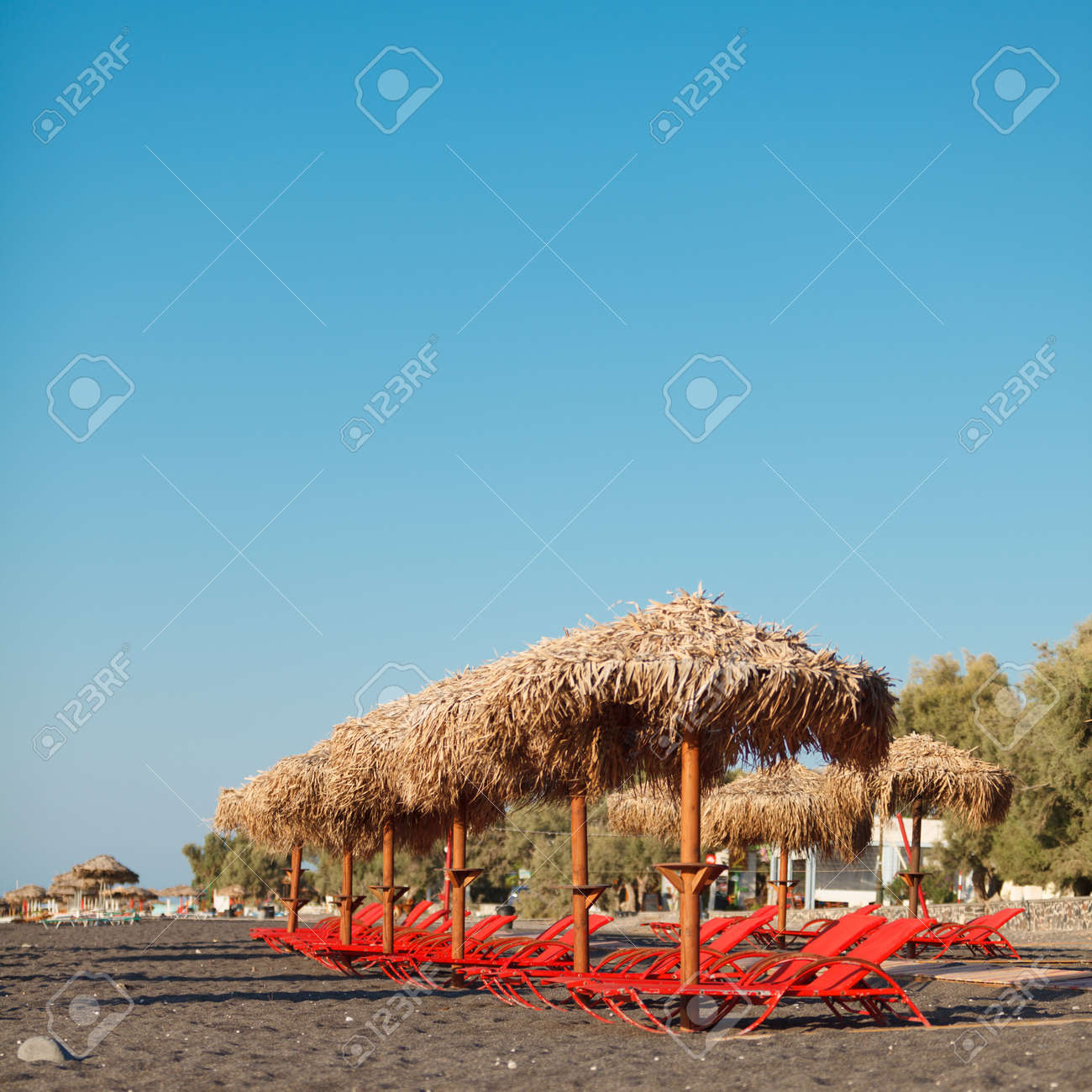 An Umbrellas And Sun Bathing Chairs On The Black Beach Of Perissa ...