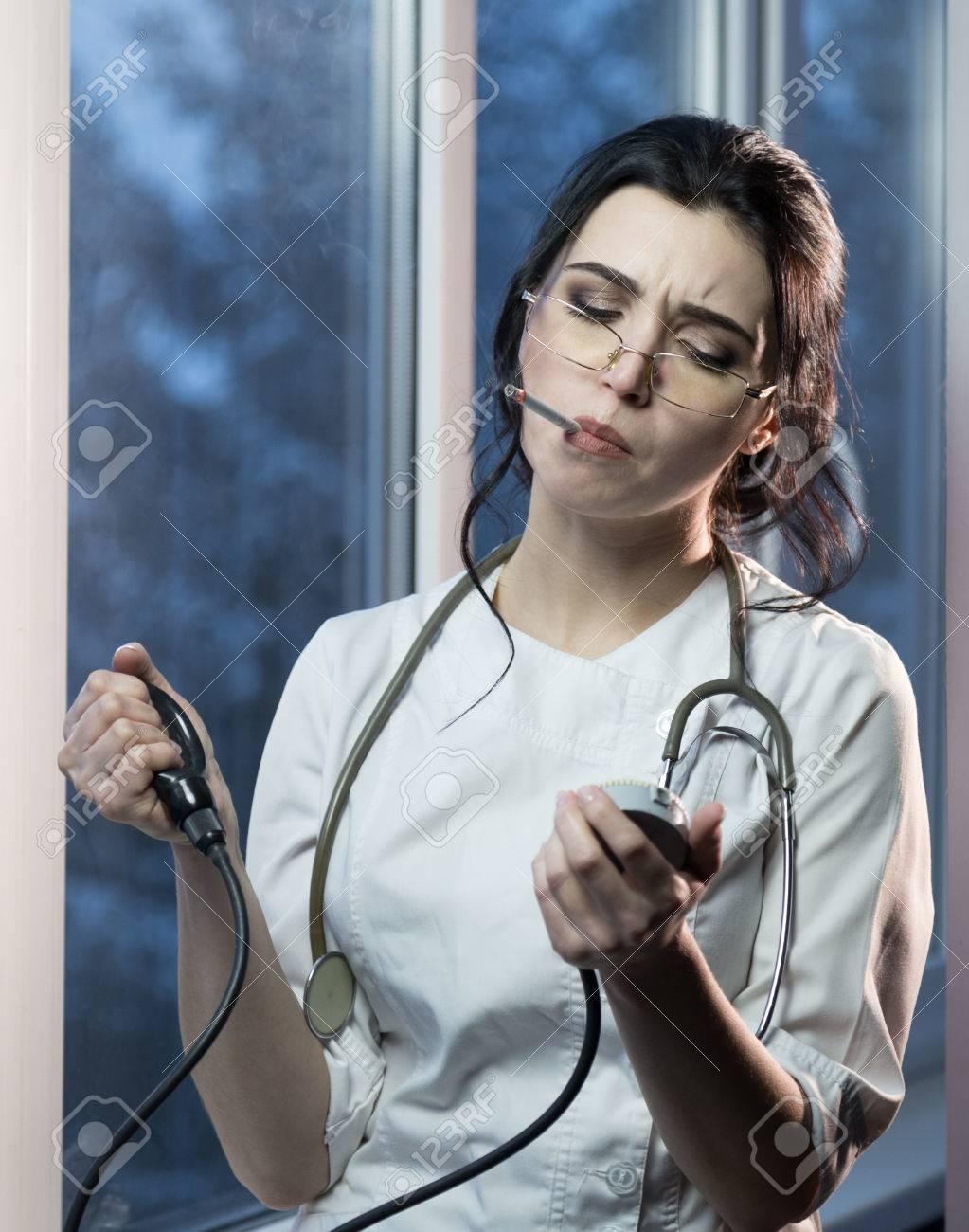 https://previews.123rf.com/images/studio2sim/studio2sim1704/studio2sim170400008/75682224-brunette-freche-weibliche-krankenschwester-in-uniform-die-eine-zigarette-ma%C3%9Fnahmen-den-blutdruck-rauc.jpg