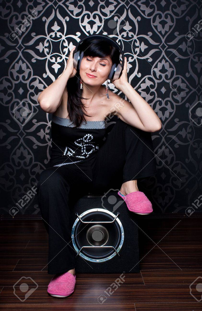 Cool girl sitting on a subwoofer with headphones on Stock Photo - 15033920