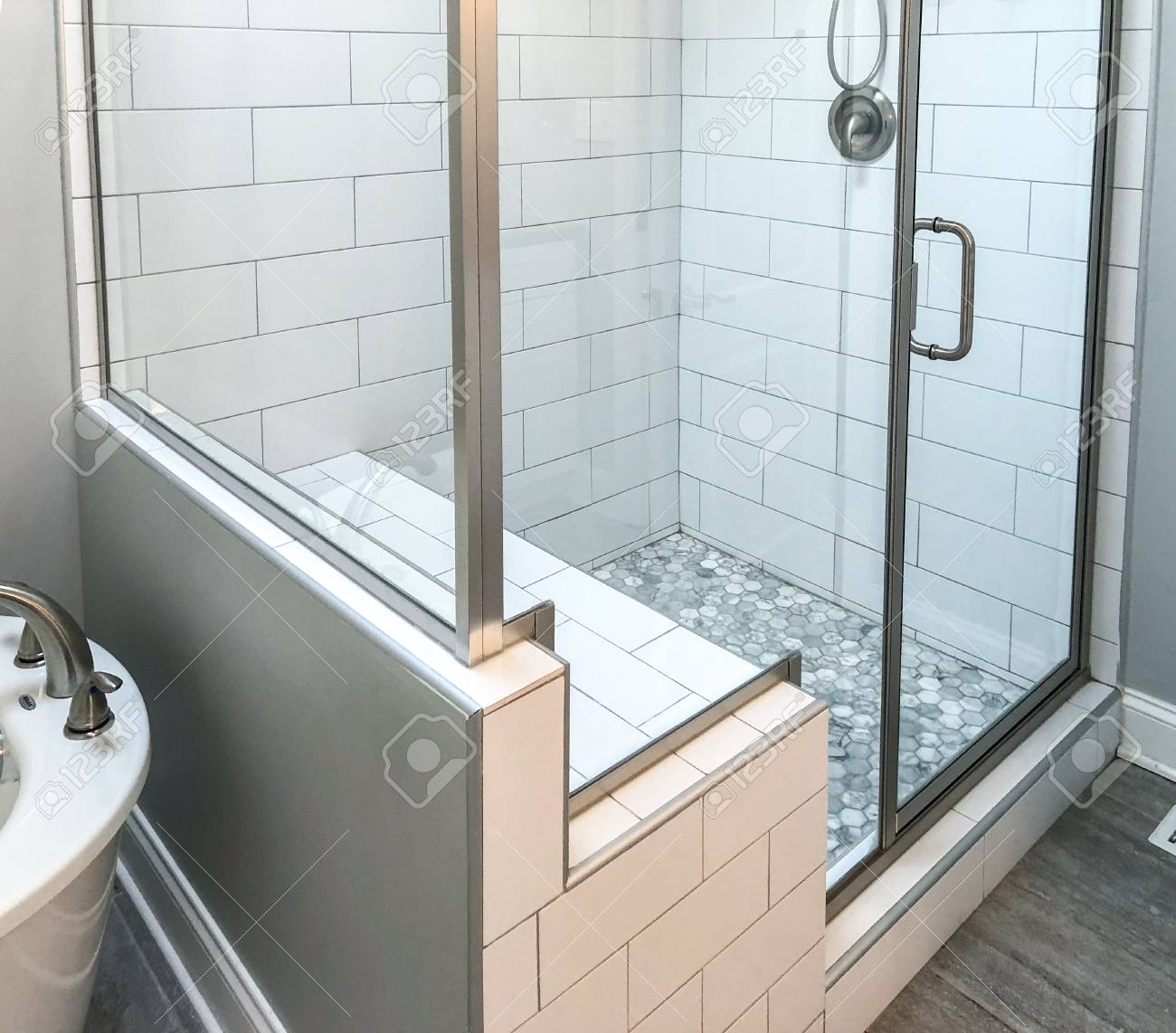 bathroom shower base with stone floor, white wall tiles