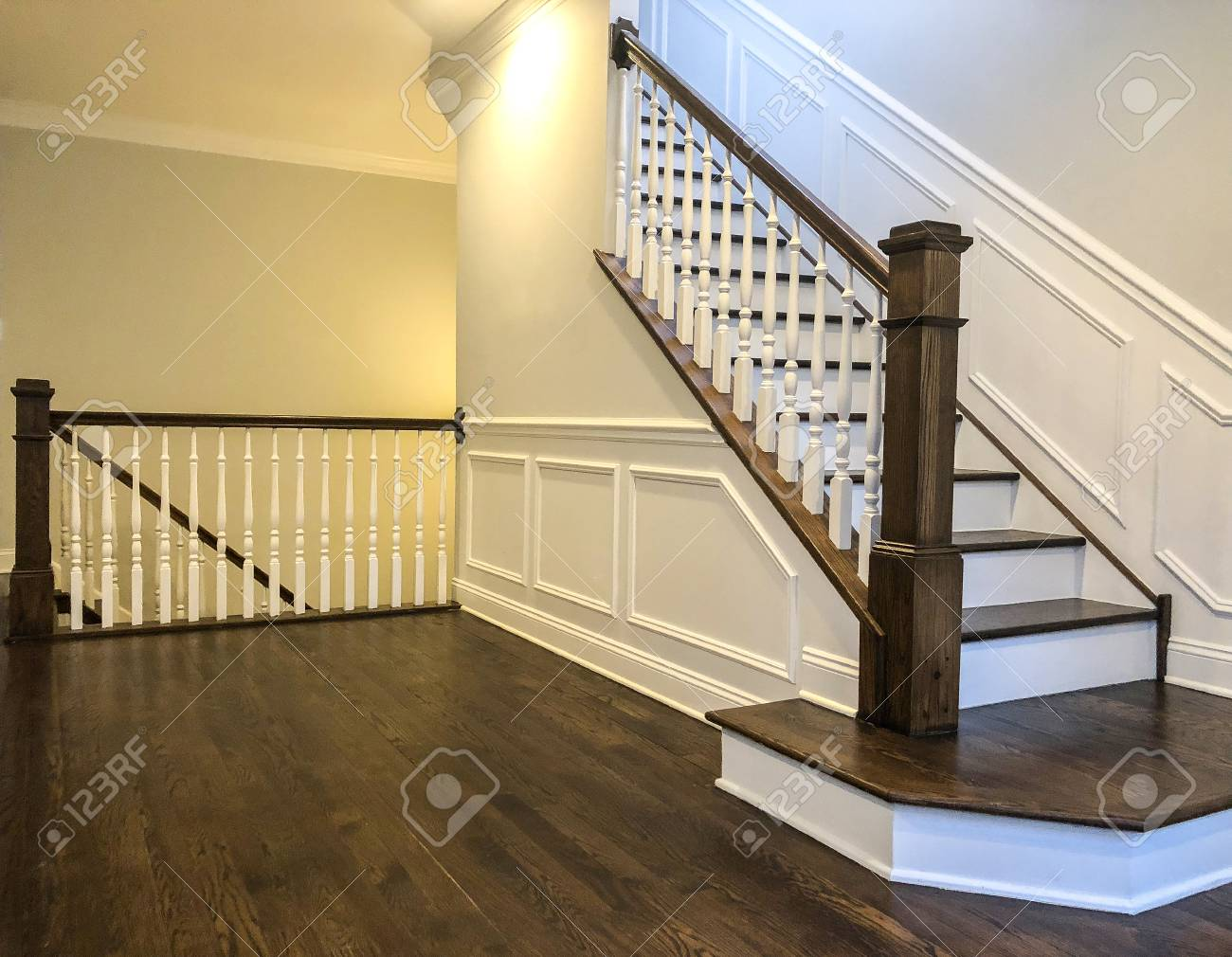 Stairs of the luxury house with white walls, wood panels in white..