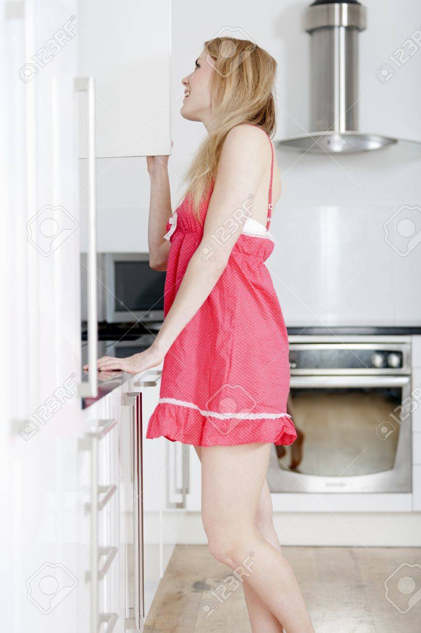 Young woman wearing pink knighty in kitchen Stock Photo - 14022929