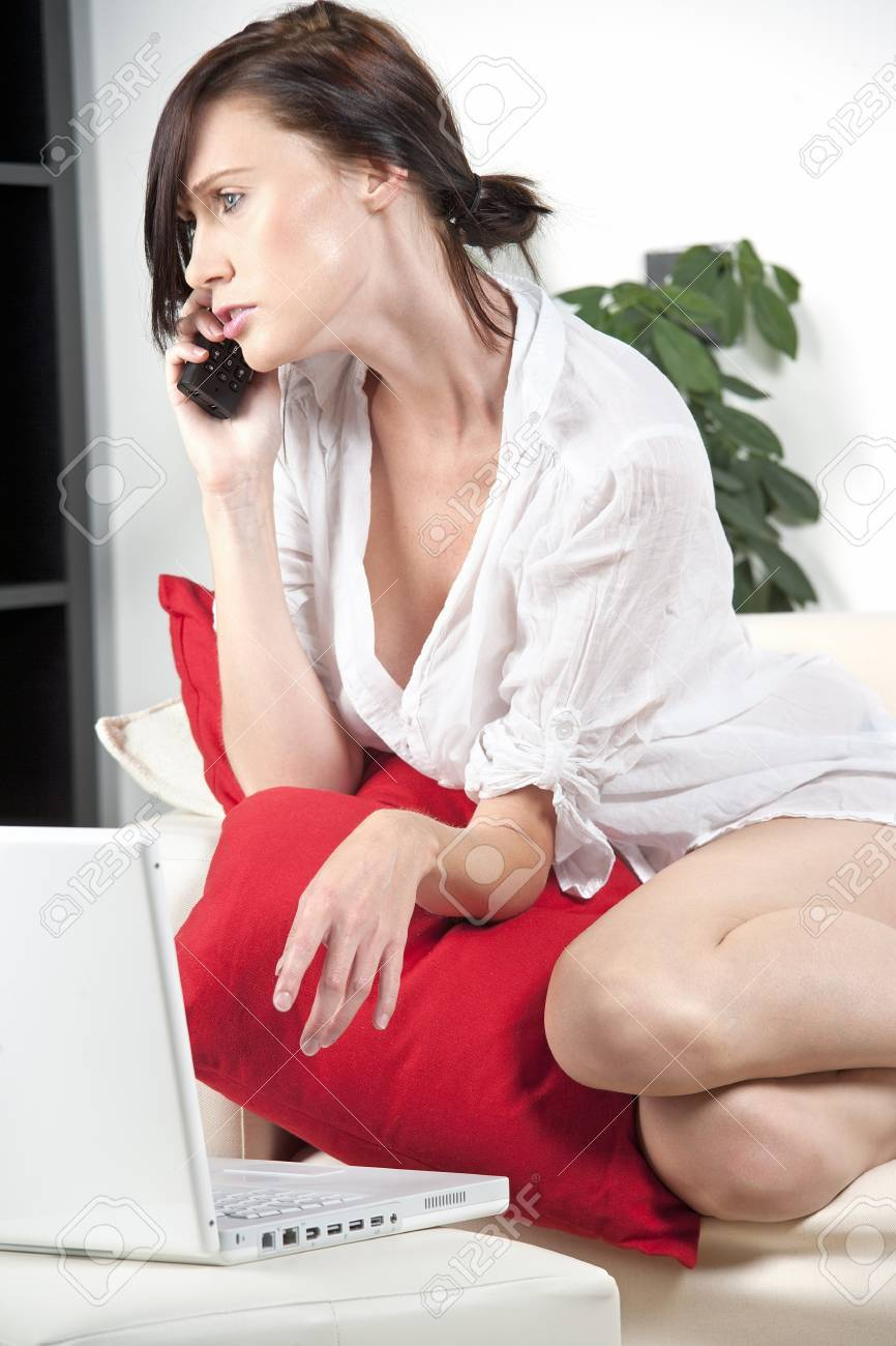 Young woman in white shirt expressing concern and worry on the phone Stock Photo - 14324886