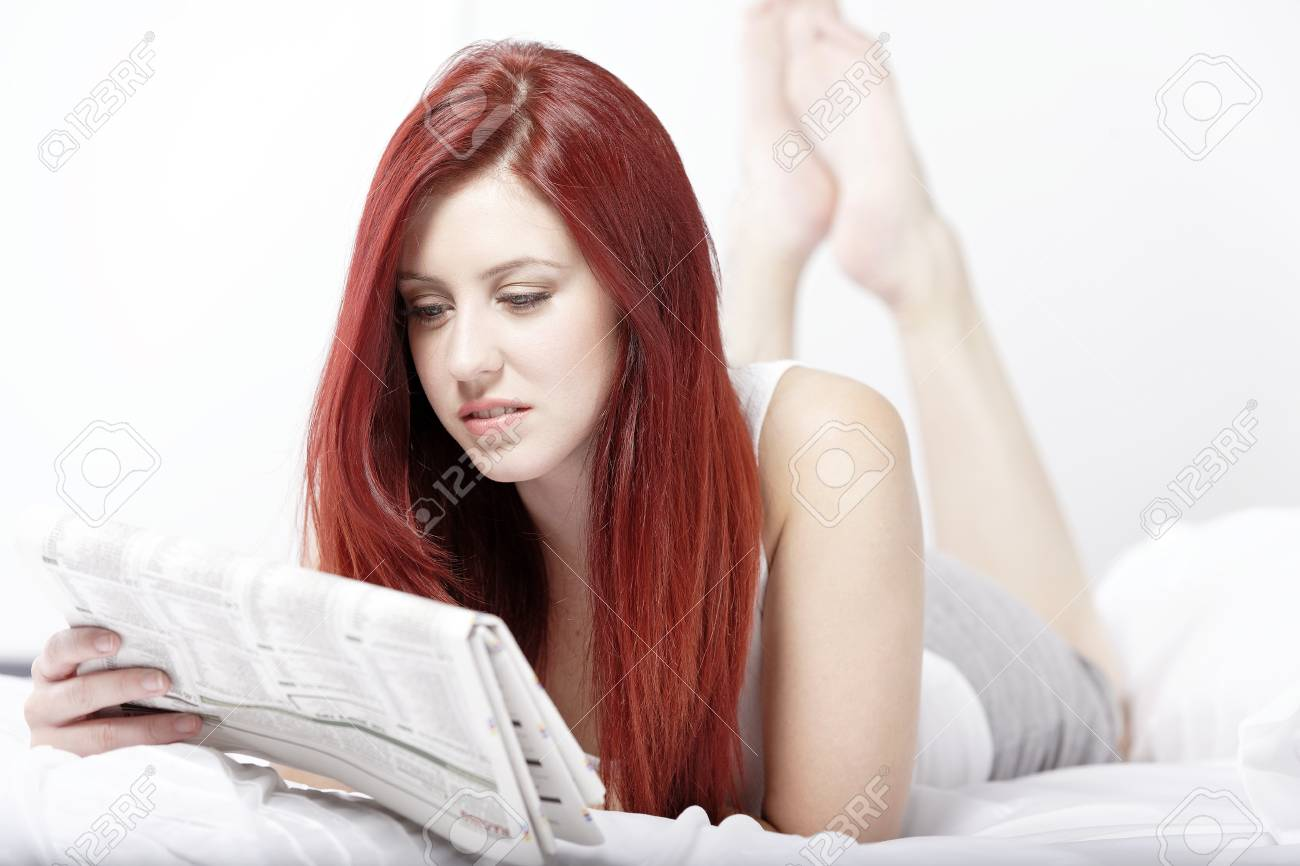 Beautiful young woman reading her news paper on her bed at home Stock Photo - 15440894