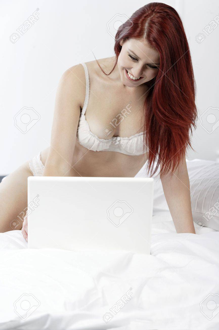 Attractive young woman working on her laptop in white underwear on her bed at home Stock Photo - 15465860