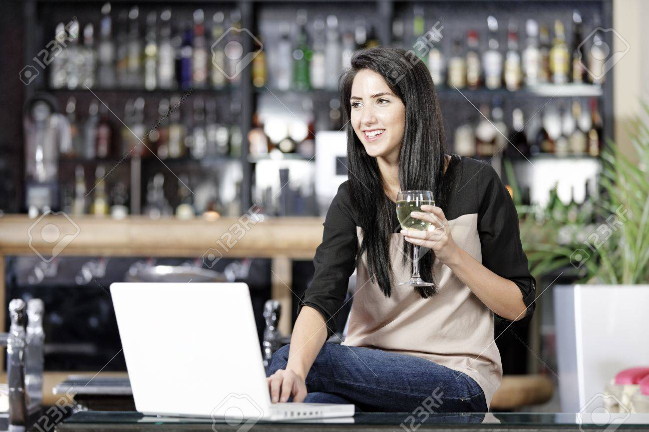 Beautiful young woman chatting with friends on her laptop while enjoying a glass of wine in a bar Stock Photo - 16217674