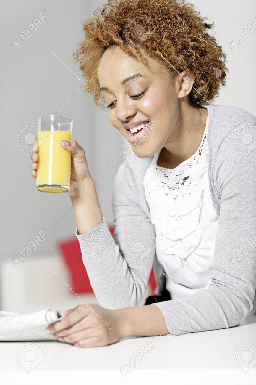 beautiful young black woman reading a newspaper while enjoying