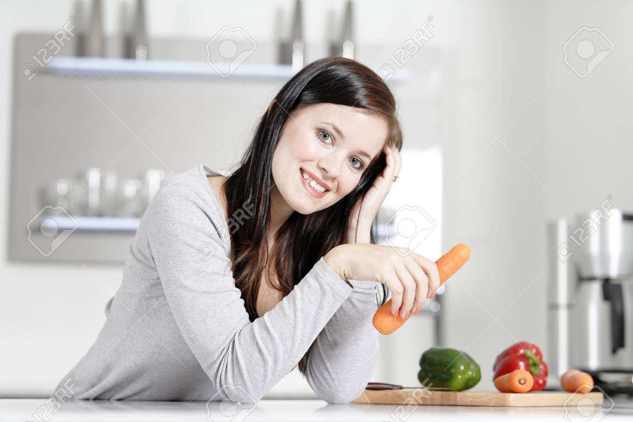Attractive young woman in her elegant kitchen with fresh vegetables ready to cook. Stock Photo - 18919733