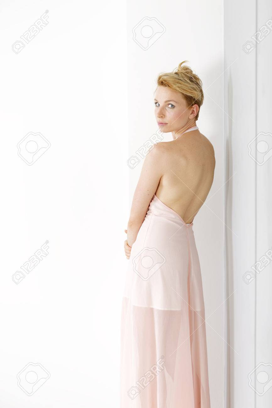 Beautiful Young Woman Wearing A Pink Evening Gown Leaning Against ...