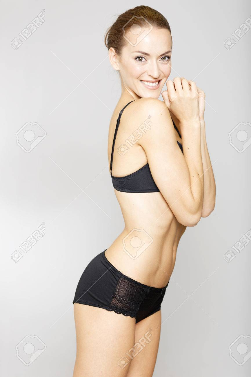 fb46c02b2d8 Attrayante jeune femme en sous-vêtements noir sur fond isolé sourire Banque  d images