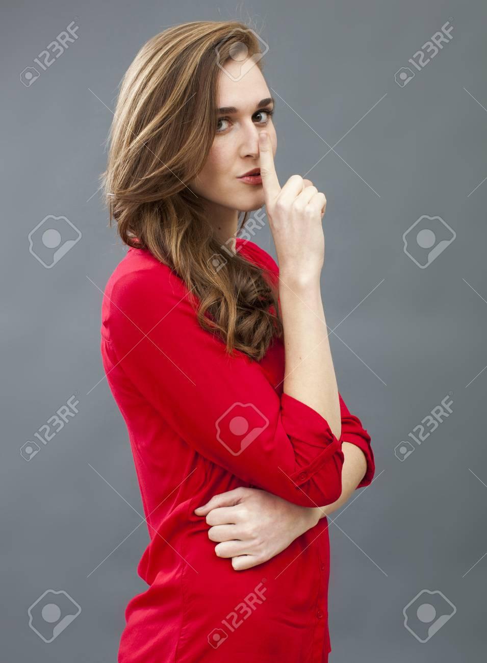 half off b2ca7 2a1c2 Concetto di segreto e tabù - 20s misteriose donna che indossa camicia rossa  che chiede il silenzio con un dito sulla bocca, girato in studio