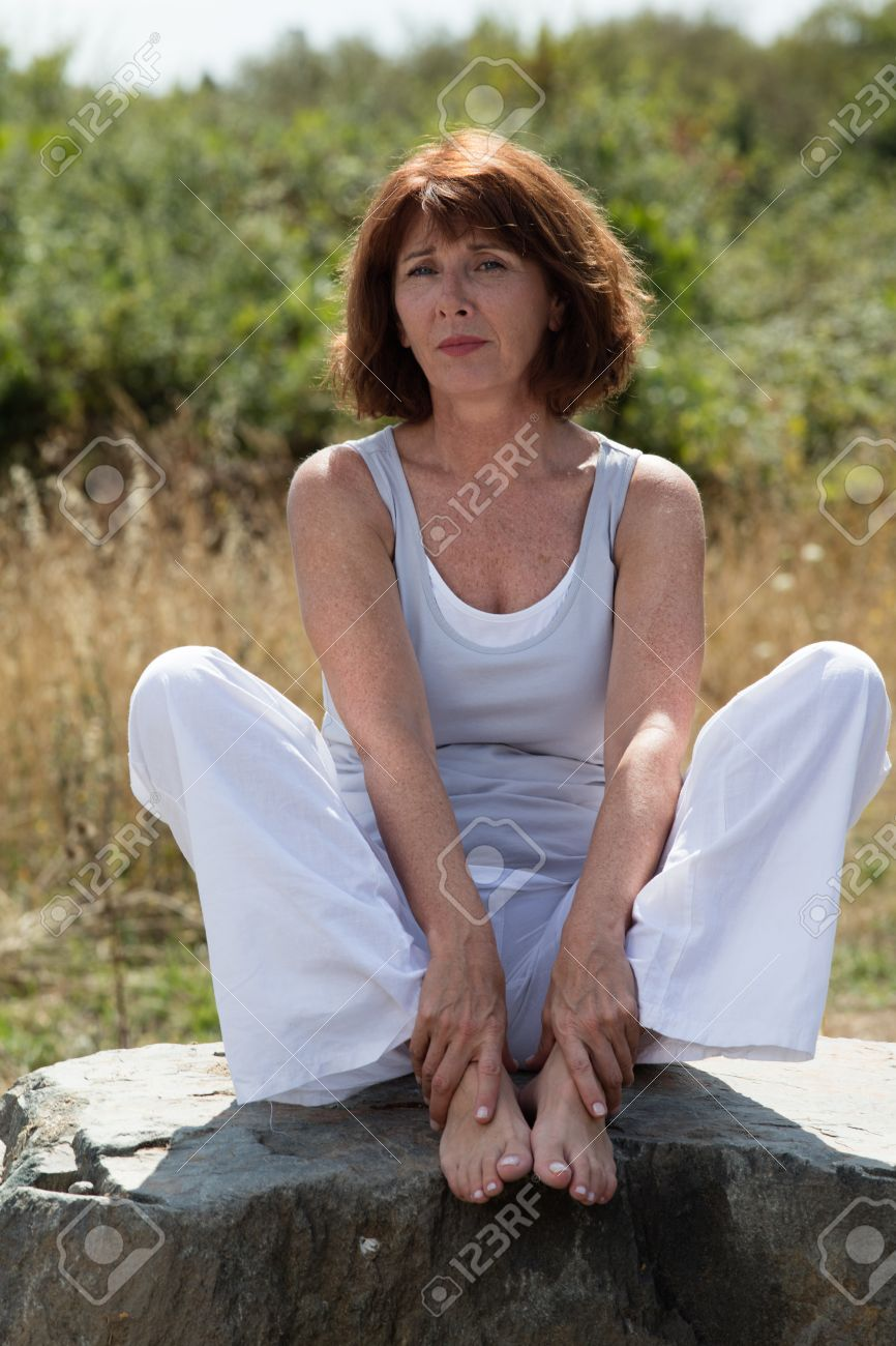 senior zen - sad 50s mature yoga woman sitting on a stone, wearing