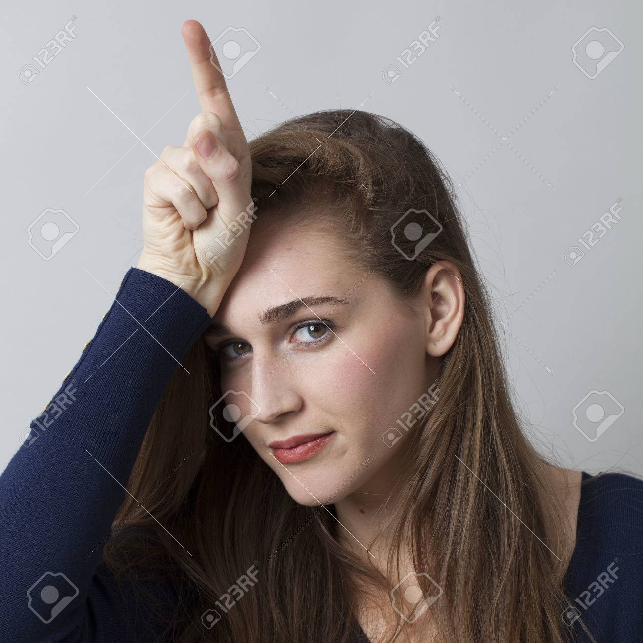 Focused young woman making the l sign on forehead for loser message cool hand gesture