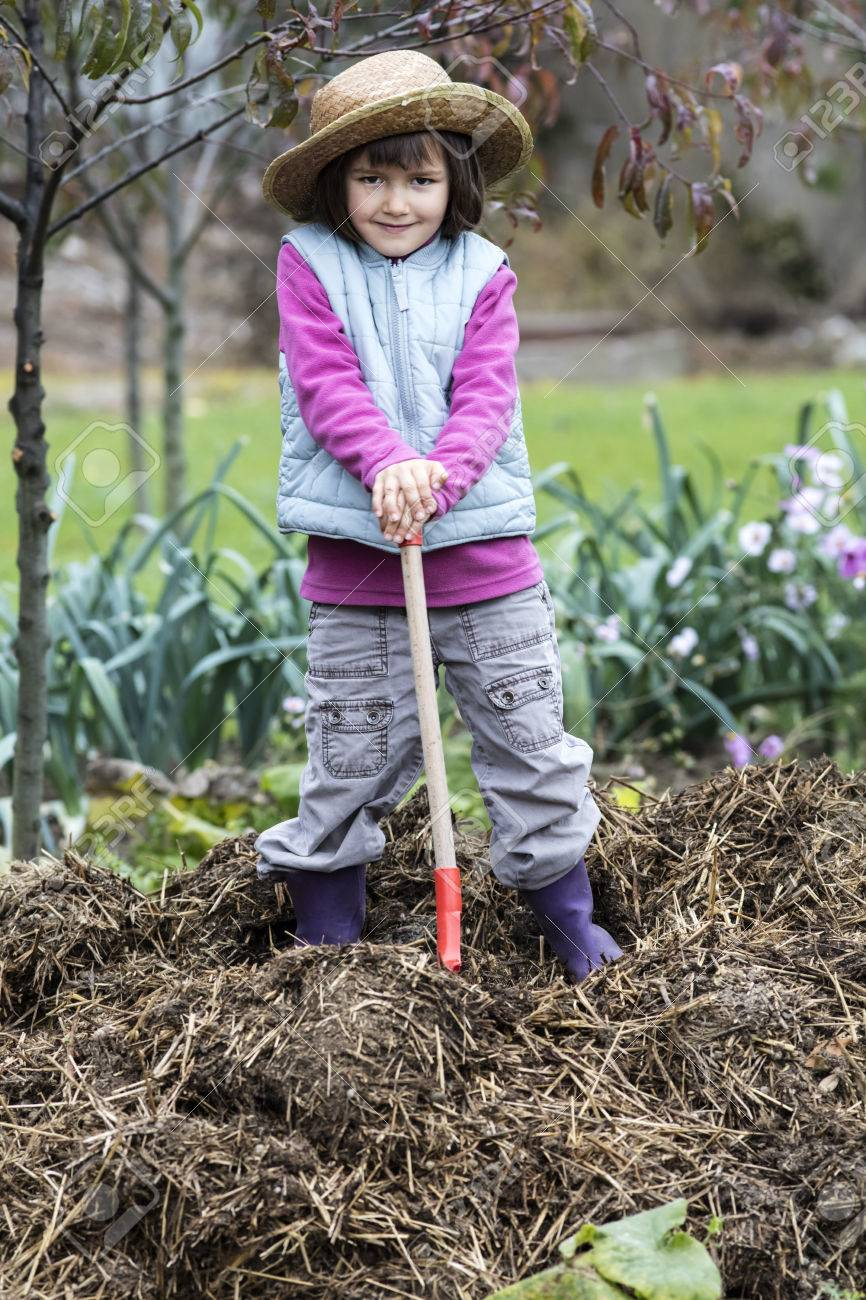 kid gardening concept thrilled child posing with a shovel on top of a pile of