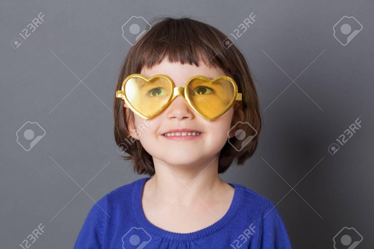 bd7d8dec95c1 fun kid glasses concept - daydreaming preschool child wearing yellow  heart-shape glasses for comic