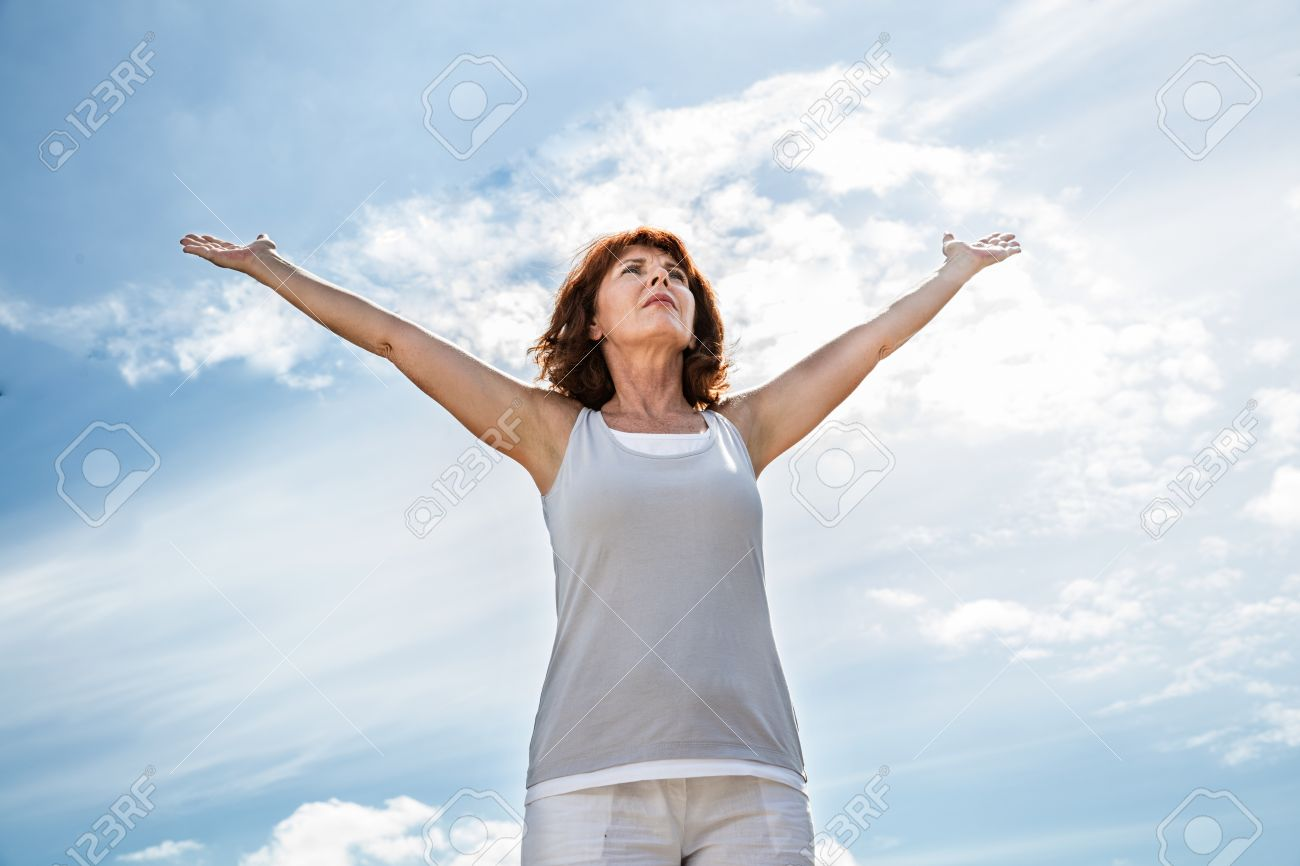 breathing outside - older yoga woman opening up her arms to exercise,practicing meditation for freedom over summer blue sky,low angle view - 51272521