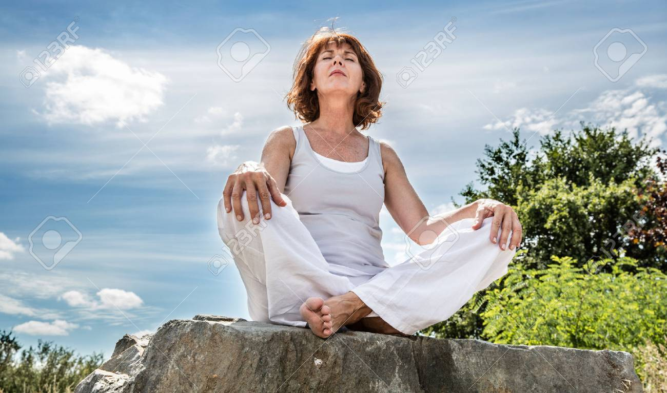 exercising outside - radiant 50s yoga woman sitting on a stone, seeking for spiritual balance with tree background,low angle view - 51653109