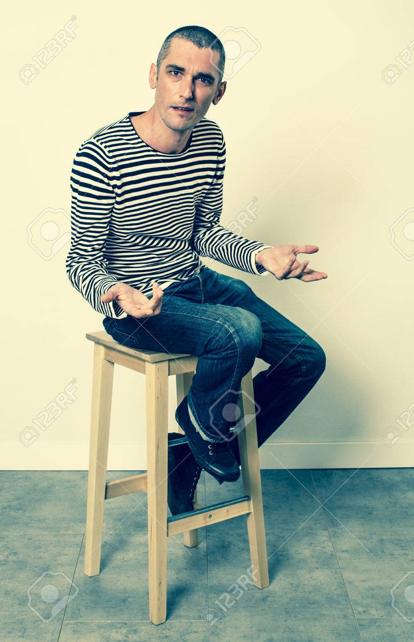 expressive body language - unhappy young man with short hair talking with his hands sitting alone on a stool, green effects - 55377200