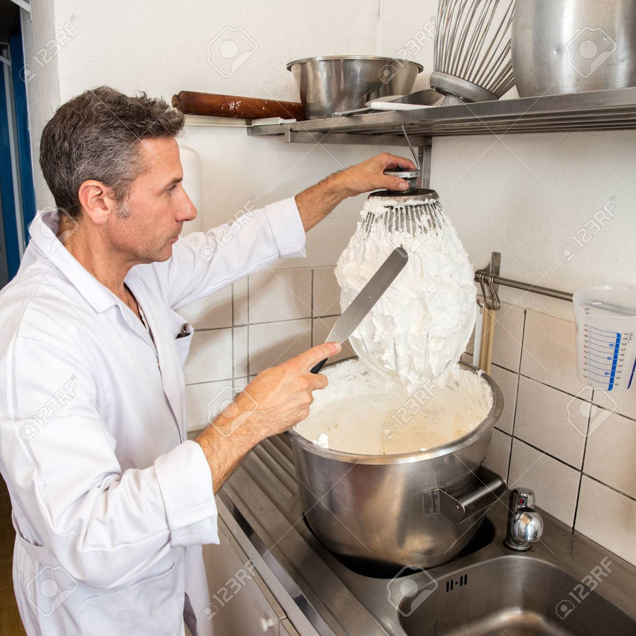 middle aged male professional cook cleaning a big whisk from stock