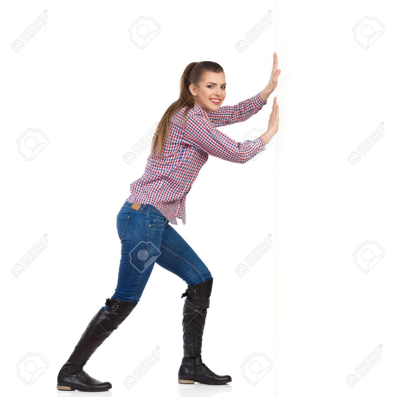 Sonriente mujer joven en pantalones vaqueros, botas negras y camisa de leñador empujando una pared blanca y mirando a la cámara. Vista lateral, tiro