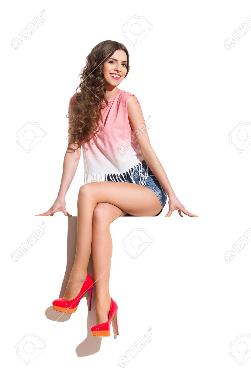 smiling sexy woman in pink top, jeans shorts and red high heels