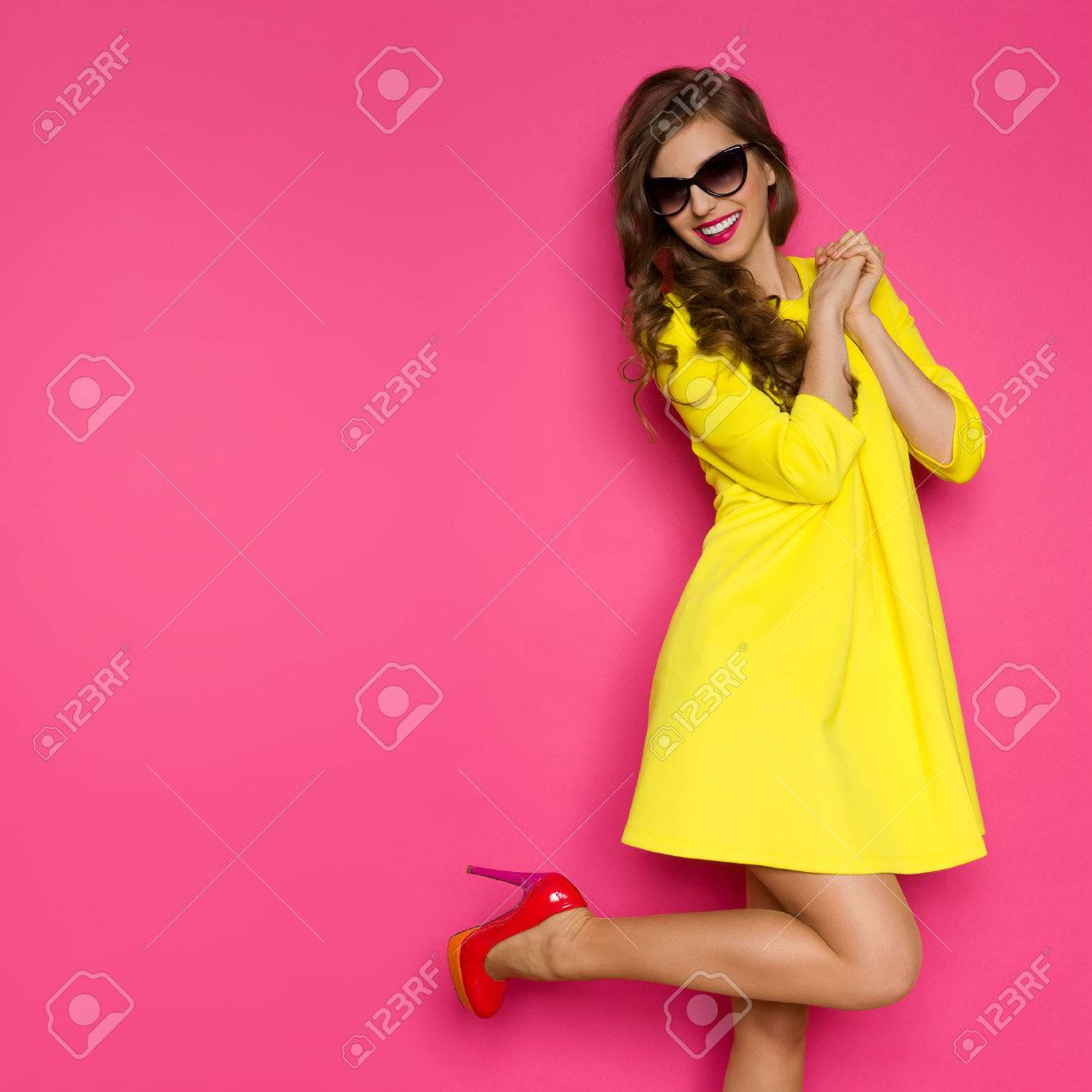 Excited girl in yellow mini dress posing on one leg against pink background. Three quarter length studio shot. - 53386056