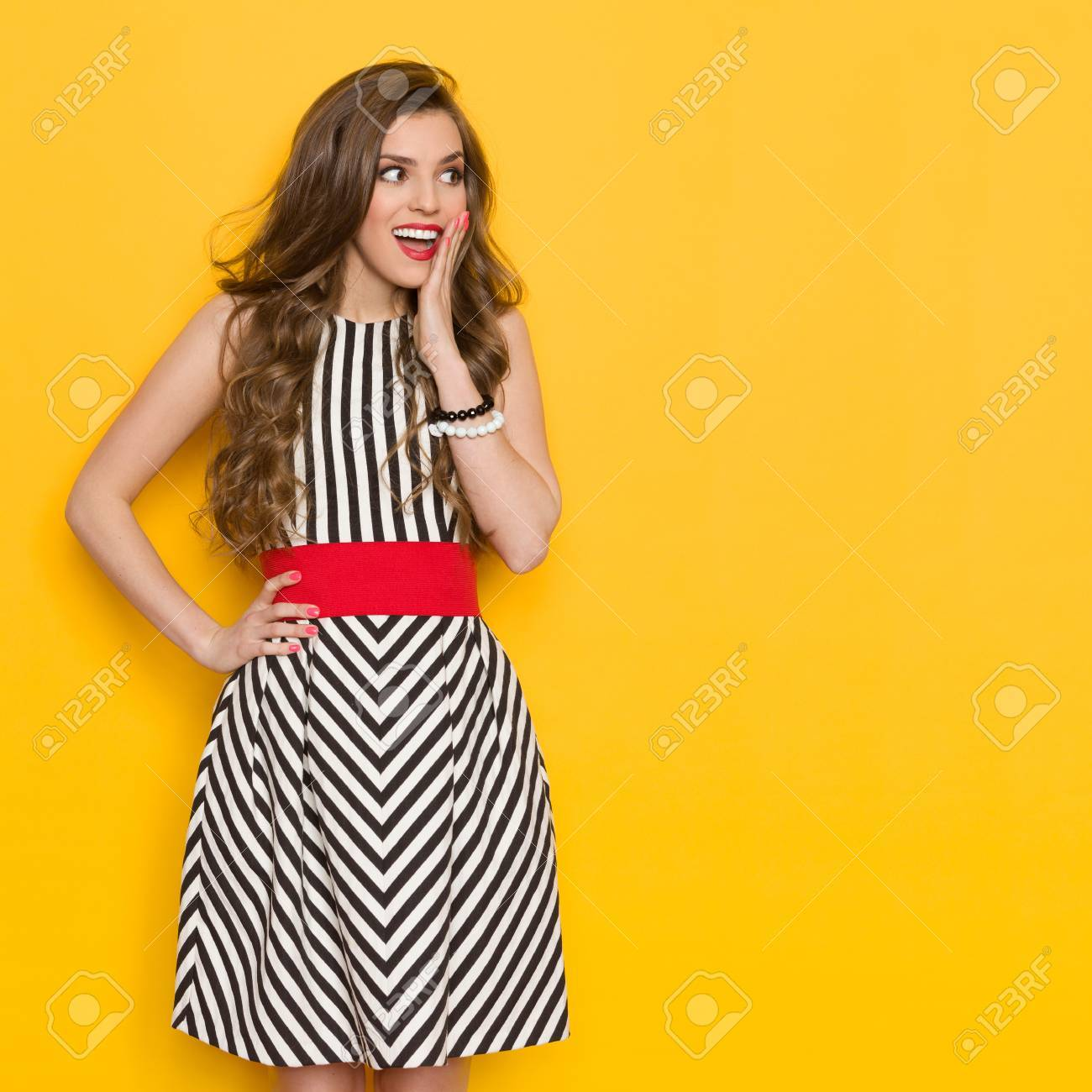 Excited beautiful young woman in black and white striped dress posing with  hand on hip 6ef065a35