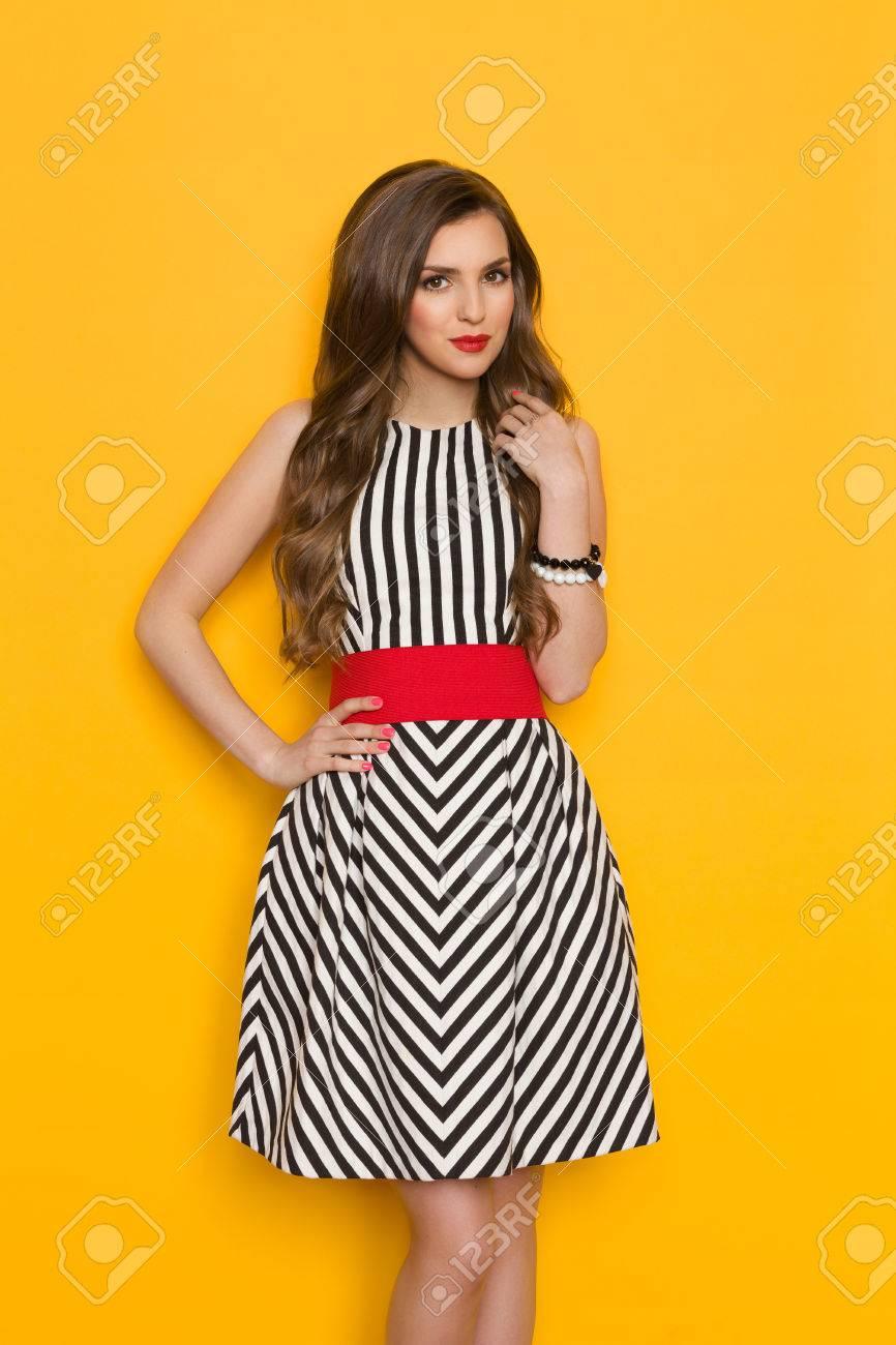 991212a847b8 Banque d images - Belle jeune femme en robe rayée noir et blanc et ceinture  rouge posant avec la main sur la hanche. Trois studio trimestre longueur  tourné ...