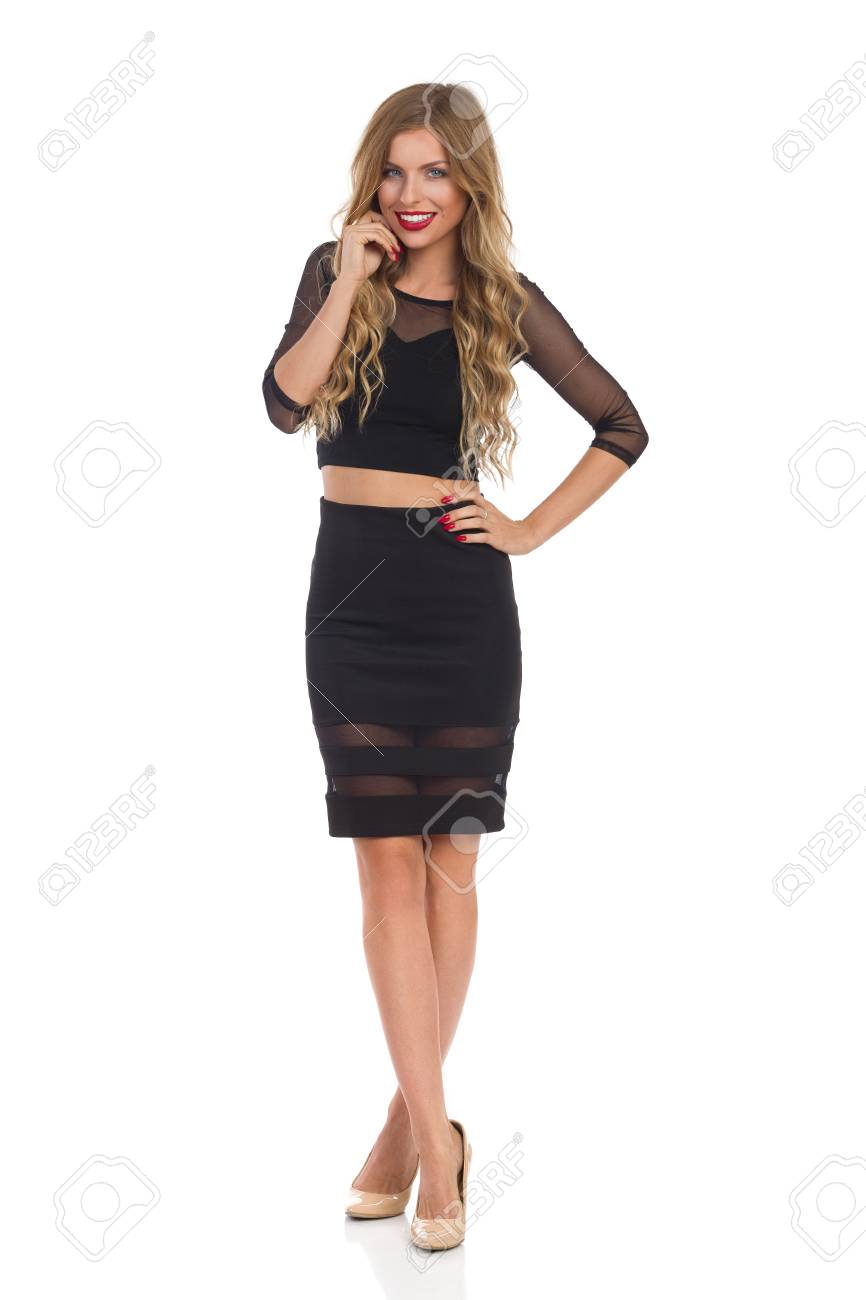 b5ab5e84f86 Banque d images - Belle jeune femme blonde en robe noire et talons hauts  beige debout avec les jambes croisées et souriant.