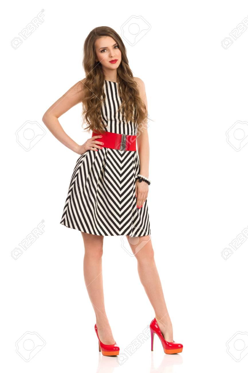 lindo baratas verse bien zapatos venta código promocional Mujer joven alegre con cabello largo castaño posando en vestido de rayas  blanco y negro y tacones altos. Tiro integral del estudio aislado en blanco.