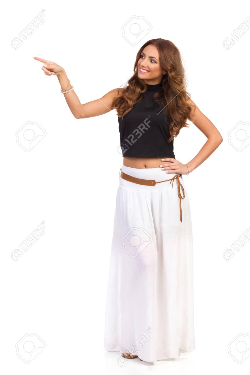 98fe7994f3 Foto de archivo - Mujer atractiva sonriente en falda blanca larga y top  negro que señala y que mira lejos