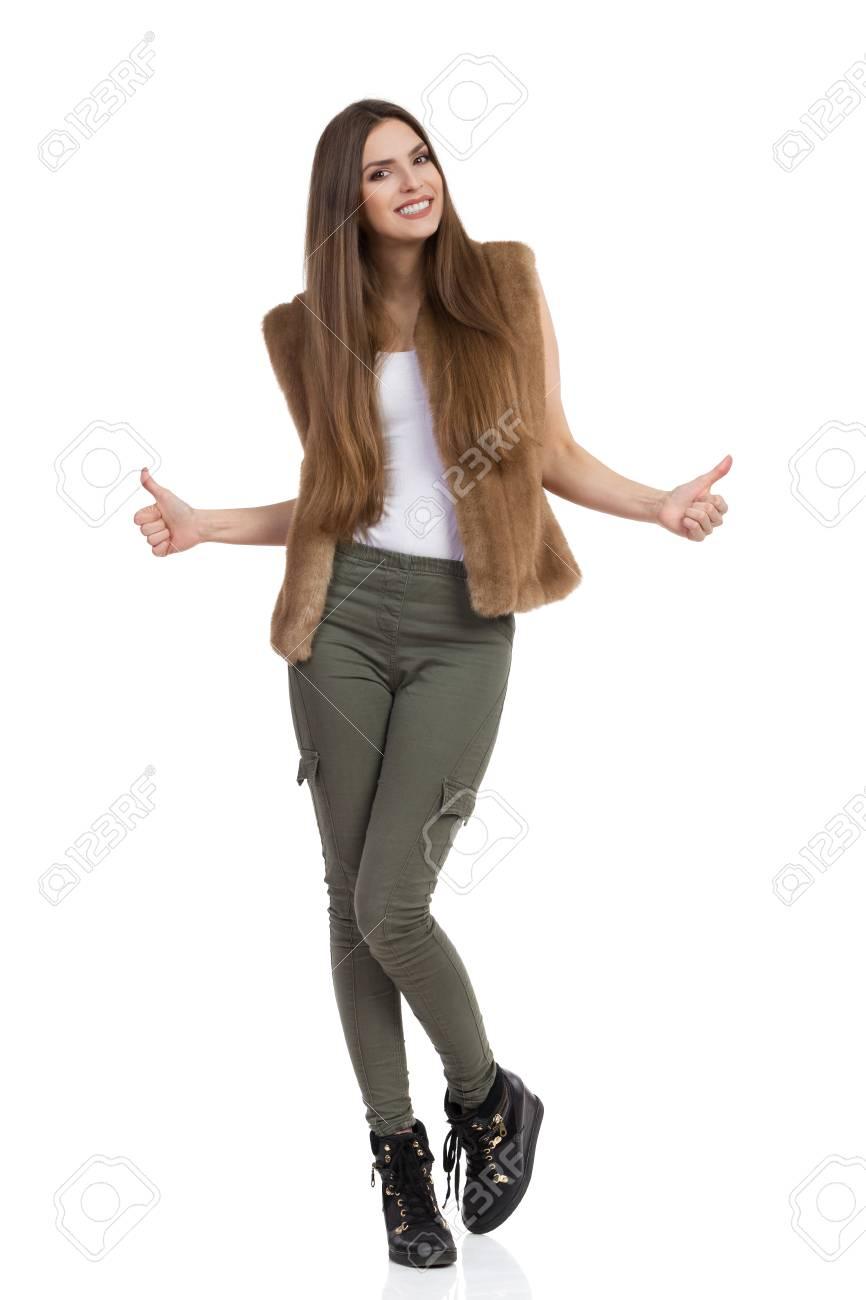 Joven Y Bella Mujer En Chaleco De Piel Marron Pantalones De Color Caqui Y Botas Negras De Pie Y Mostrando Los Pulgares Para Arriba Tiro De Estudio De Longitud Completa Aislado En