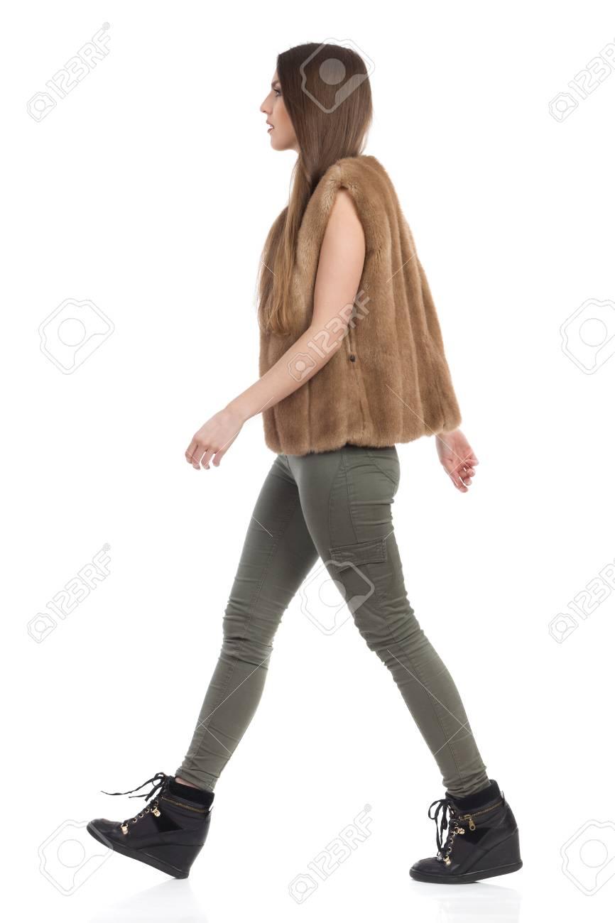 Mujer Joven Con Chaleco De Piel Marron Pantalones Caqui Y Botas Negras Caminando Y Mirando A Otro Lado Vista Lateral Tiro Integral Del Estudio Aislado En Blanco Fotos Retratos Imagenes Y Fotografia