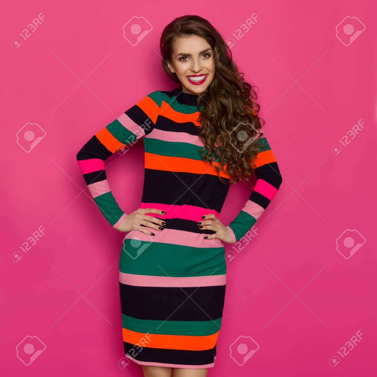 f7252d066518 Beautiful young woman in colorful vibrant striped dress is holding hands on  hip
