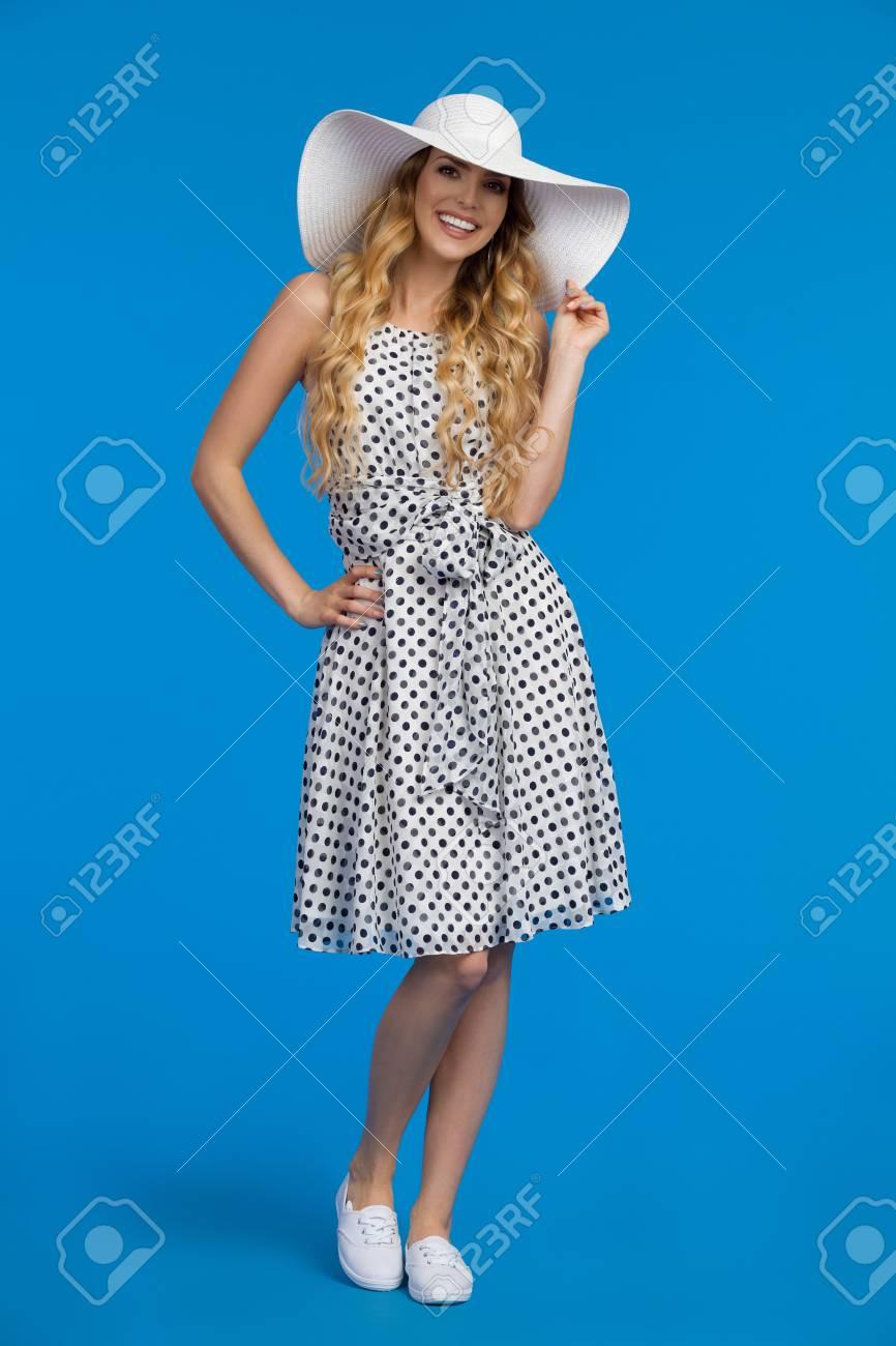 Banque d images - Belle jeune femme en robe d été blanche, espadrilles et  chapeau de soleil est debout, regardant la caméra et souriant. d853c66aa5d5