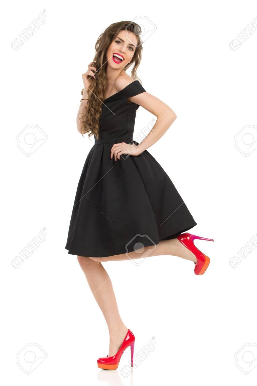 La Mujer Joven Hermosa En Vestido De Coctel Negro Elegante Y Los Tacones Altos Rojos Se Está Colocando En Una Pierna Y Está Riendo Estudio Integral