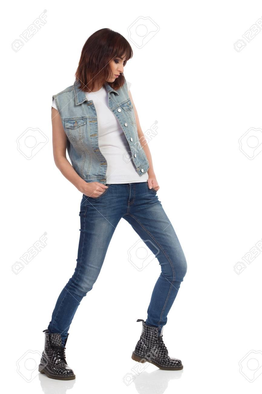 La Mujer Joven En El Chaleco De Los Pantalones Vaqueros Y Las Botas Negras Se Esta Colocando Las Piernas Separadas Y Esta Mirando Hacia Abajo Tiro Integral Del Estudio Aislado En Blanco