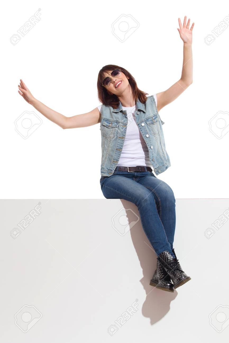 Giovane donna in occhiali da sole, gilet jeans e stivali neri è seduto su una cima, guardando lontano e tenendo le braccia tese. Colpo di studio