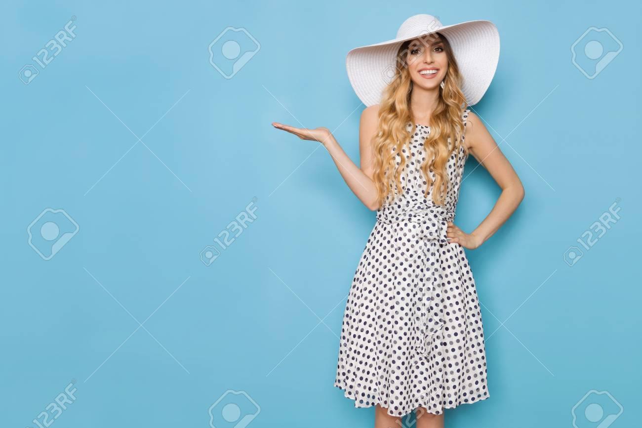bbec14095830 Bella giovane donna in abito bianco punteggiato di estate e cappello da  sole è in piedi con la mano alzato