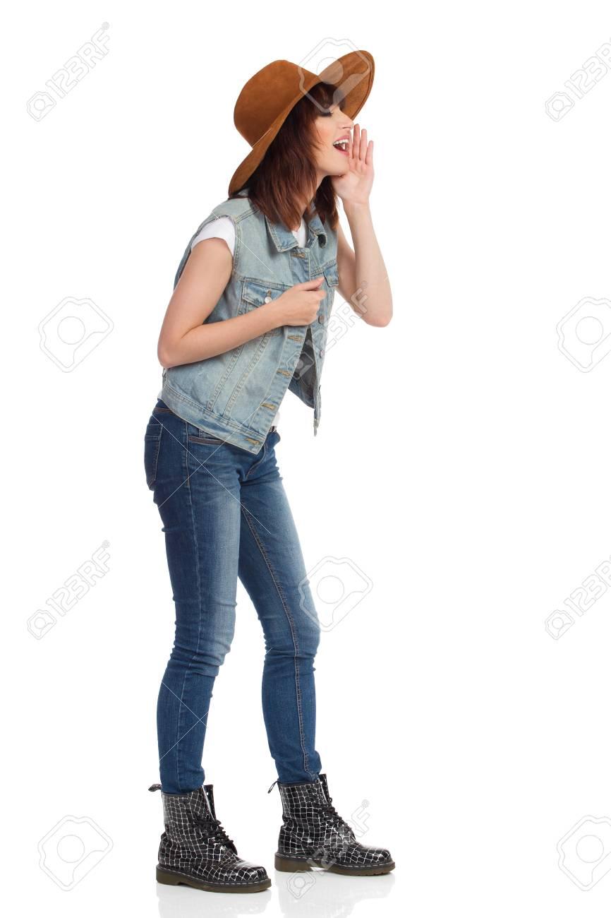 Giovane donna in gilet di jeans, stivali neri e cappello in pelle scamosciata marrone è in piedi, tenendo la mano sul mento e gridando. Vista