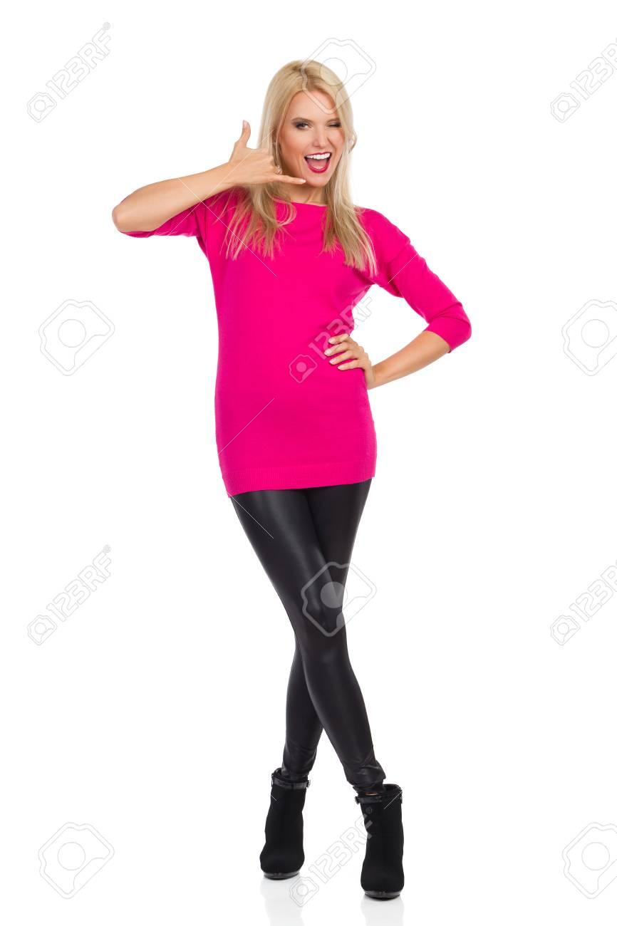 Bella donna bionda in leggings neri, tacchi alti e maglione rosa è in piedi, mostrando, chiamami segno della mano e ammiccanti. Vista frontale. Colpo