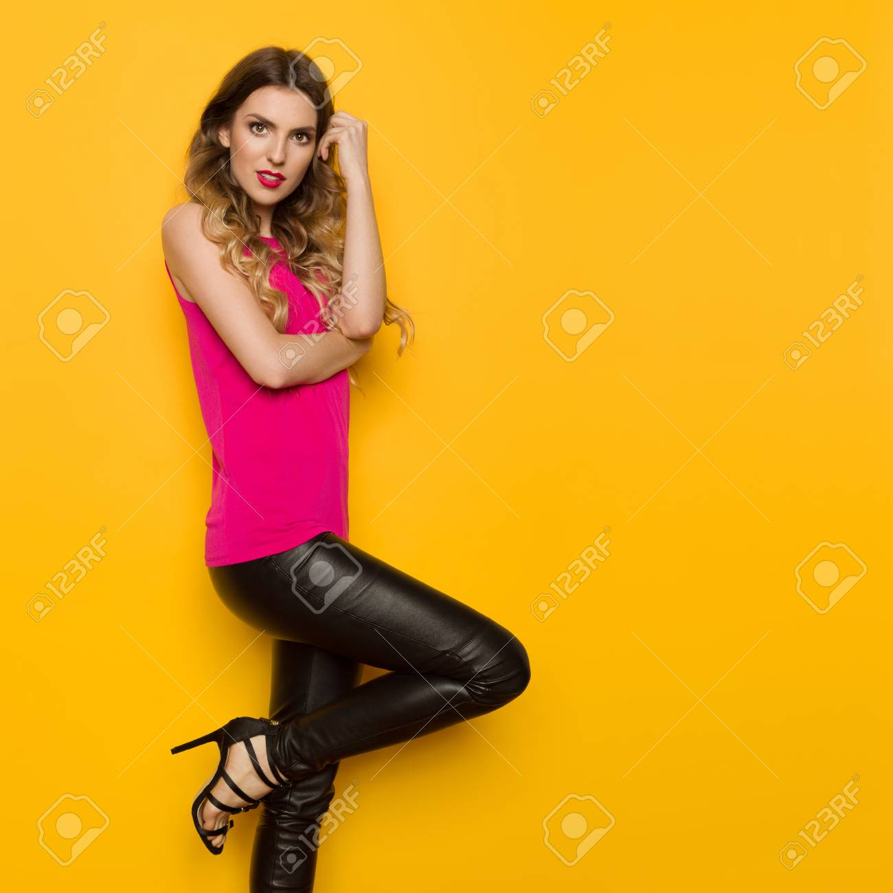 2b51936fe6f Beautiful young woman in pink top, black leather pants and high..
