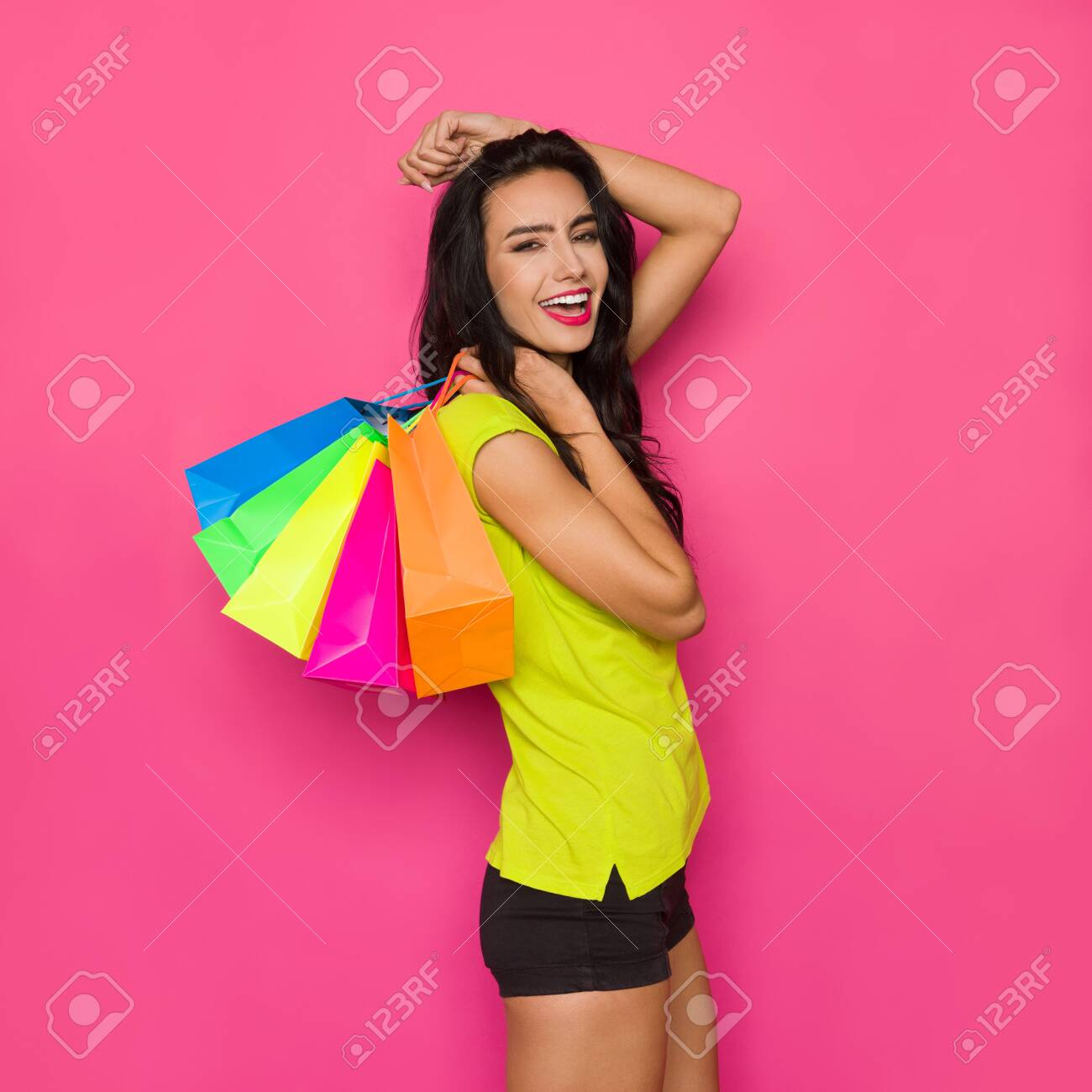 Happy beautiful young woman in vibrant green shirt and black shorts is holding colorful shopping bags on her shoulder and shoutng. Three quarter length studio shot on pink background. - 123523452
