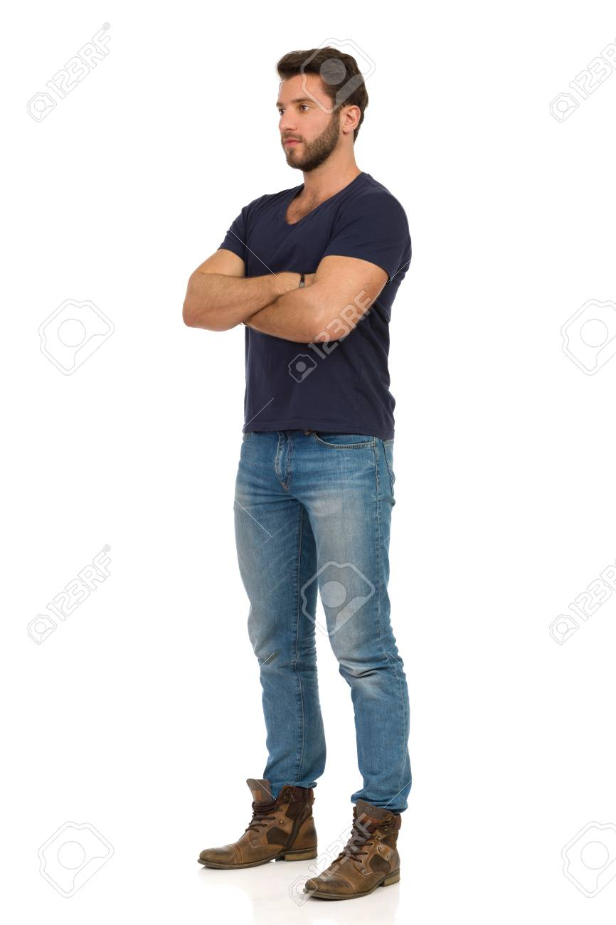 Serious handsome man in jeans, boots and blue t-shirt is standing with arms crossed and looking away. Full length studio shot isolated on white. - 125166568