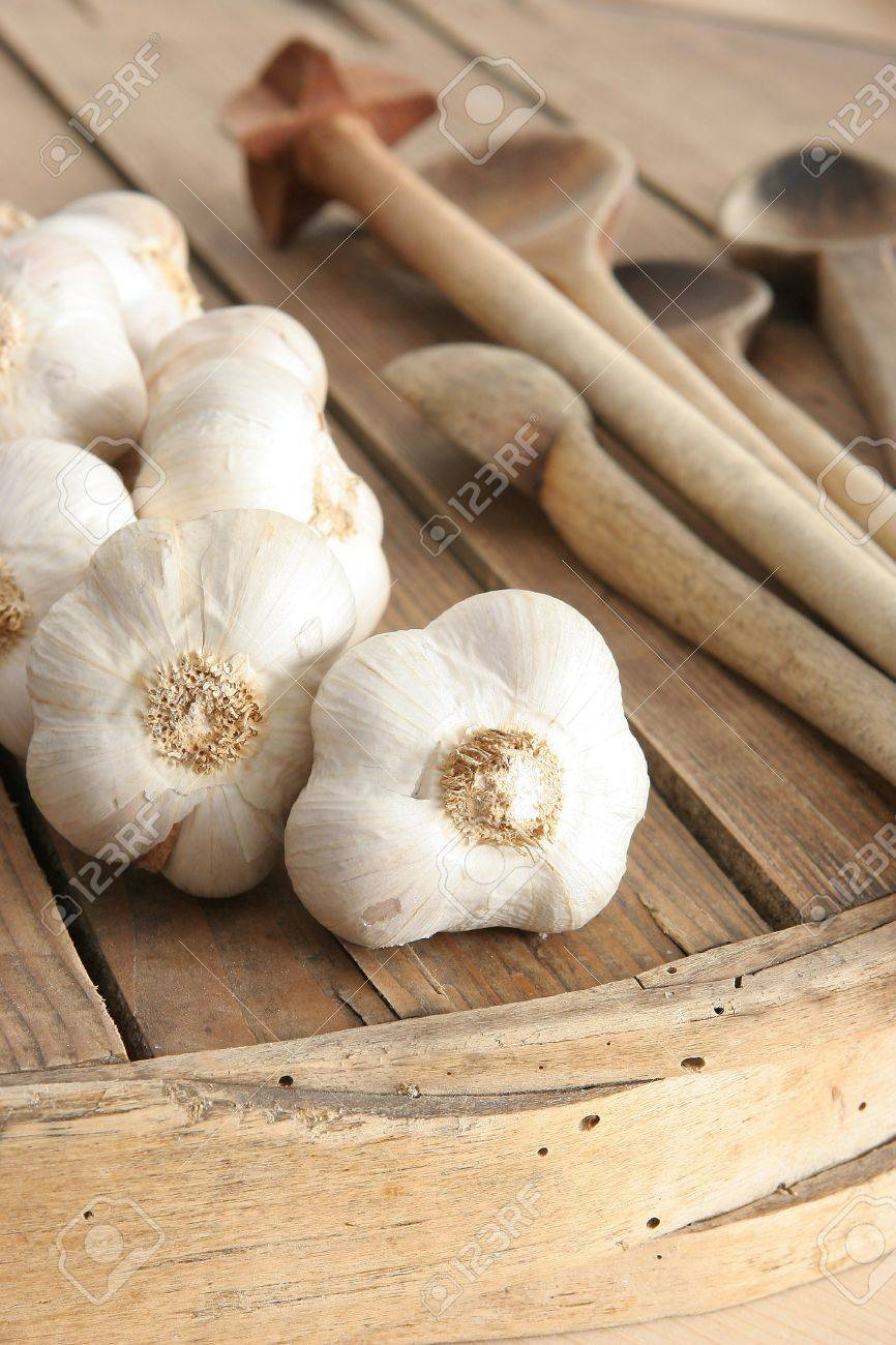 garlic, old boards and wooden utensils in the background Stock Photo - 13272121