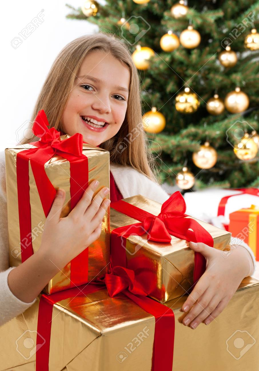 Beautiful young blonde girl holds golden gift box with red ribbon  Christmas tree with golden glass-balls in background Stock Photo - 16613843