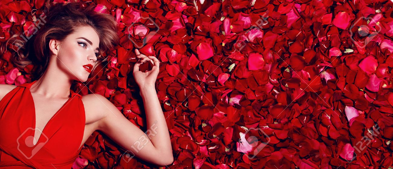 Valentine's Day. Loving girl. The girl in a red dress lying on the floor in the petals of red roses. Background of red rose petals. Red lipstick on the lips from the beautiful girl. - 70651790